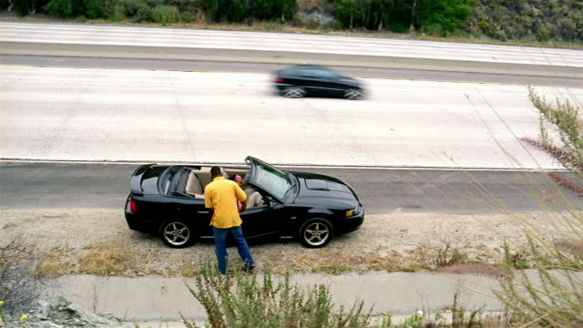 high angle wide shot man helping woman into convertible / getting into car on the side of route 2 / glendale, ca - マナー点の映像素材/bロール