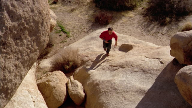 stockvideo's en b-roll-footage met high angle wide shot man jumping from boulder to boulder / joshua tree national park / california - joshua tree national park