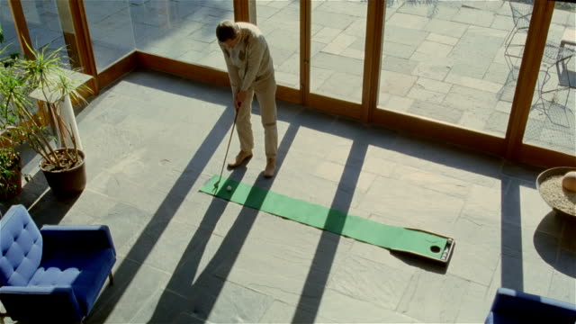 vidéos et rushes de high angle wide shot man practicing putting on indoor green/ making shot/ solebury, pennsylvania - un seul homme d'âge moyen