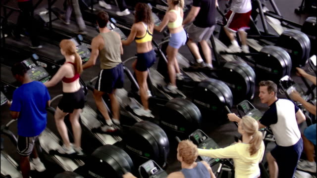 high angle wide shot men and women using elliptical trainers and treadmills in gym - cross trainer stock videos and b-roll footage