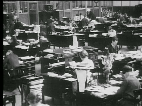 stockvideo's en b-roll-footage met b/w 1927 high angle wide shot men + women working at desks in large office / industrial - 1927