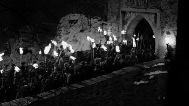 high angle wide shot mob carrying torches across bridge into castle at night - anger stock videos & royalty-free footage