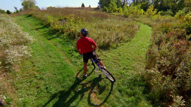 high angle wide shot mountain biker speeding up to fork in trail / pausing to decide which way / veering right - choice stock videos & royalty-free footage