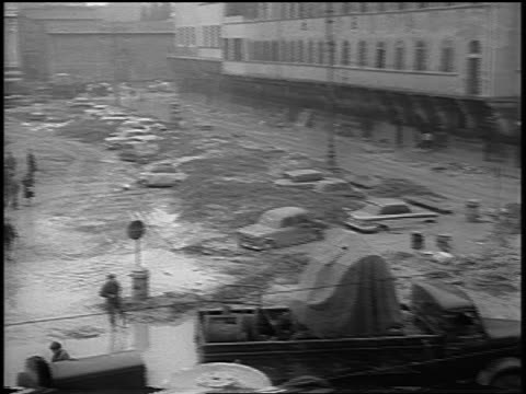 b/w 1966 high angle wide shot pan mudfilled plaza with relief workers trucks after flood / florence italy - 1966 stock videos & royalty-free footage