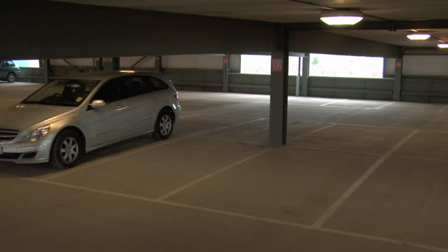 High angle wide shot mugger running toward woman and snatching her purse in parking garage/ England