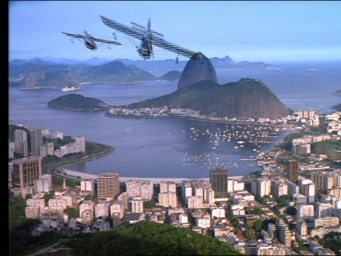 high angle wide shot of 3 airplanes flying over Rio harbor + Sugarloaf