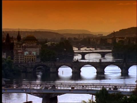 vídeos de stock, filmes e b-roll de high angle wide shot of city with river + bridges / prague / filter - ponte carlos
