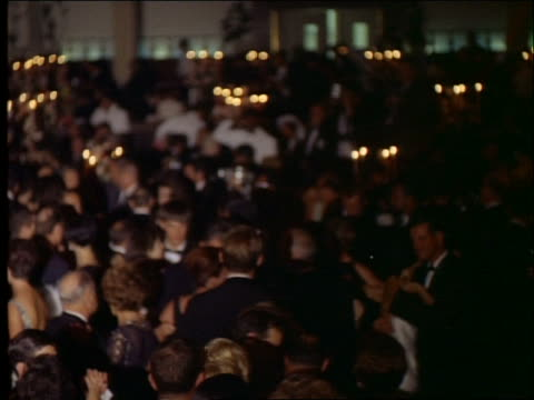1965 high angle wide shot of crowd of couples in formalwear dancing / academy awards - オスカーパーティー点の映像素材/bロール