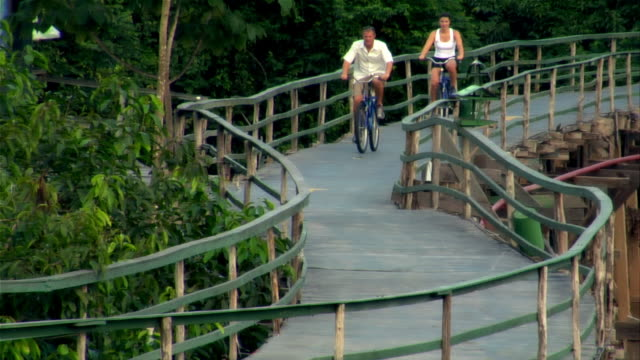 high angle wide shot of man and woman riding bicycles on wooden bridge in rainforest / the amazon, brazil - paar mittleren alters stock-videos und b-roll-filmmaterial