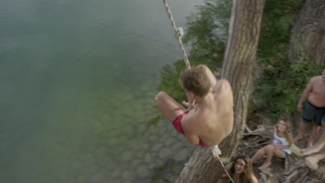 high angle wide shot of man swinging into lake / mona, utah, united states - rope swing stock videos & royalty-free footage