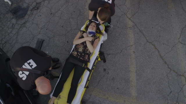 High angle wide shot of paramedics strapping victim to gurney / Pleasant Grove, Utah, United States