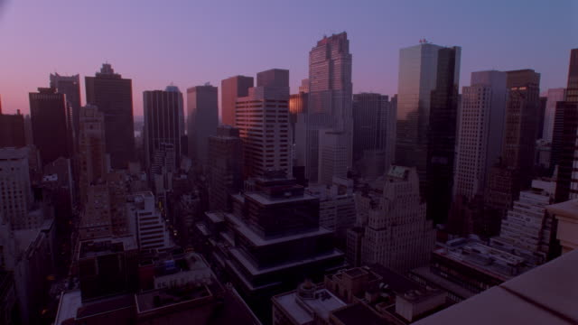 high angle wide shot of skyscrapers in midtown Manhattan - time lapse day to night / New York City