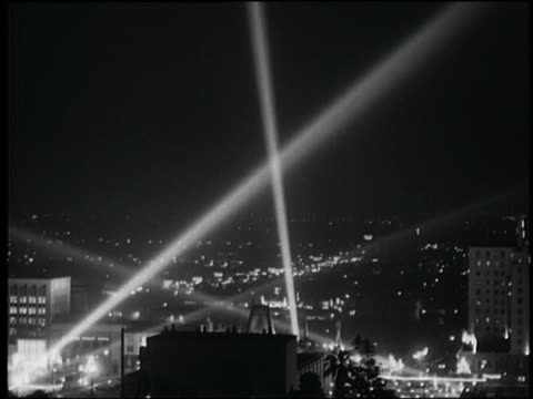 B/W high angle wide shot of spotlights over Los Angeles at night / Manns Theater in foreground