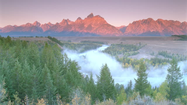 high angle wide shot of time lapse fog in snake river valley with forest, plain and teton moutains / grand teton national park, wyoming - parco nazionale del grand teton video stock e b–roll