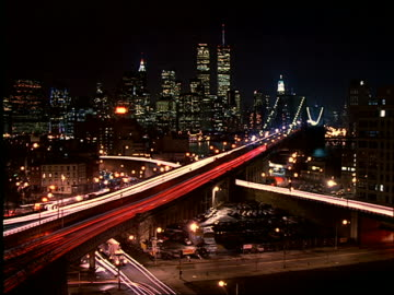 high angle wide shot of time lapse traffic on brooklyn bridge with manhattan skyline in background at night - 1997 stock videos & royalty-free footage
