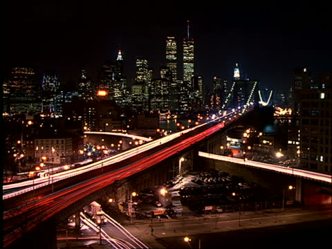 high angle wide shot of time lapse traffic on brooklyn bridge with manhattan skyline in background at night - anno 1997 video stock e b–roll