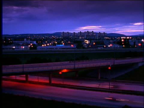 high angle wide shot of time lapse traffic on highway with overpass at dusk / vienna - ウィーン点の映像素材/bロール