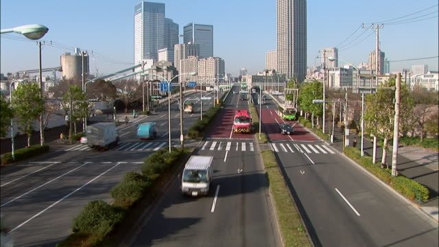 high angle wide shot of traffic on three lanes with view of skyscrapers in background / tokyo - 2005年点の映像素材/bロール