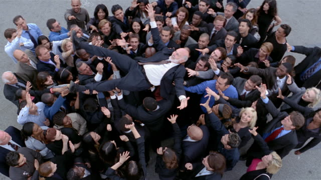 high angle wide shot older man being held up by crowd of businesspeople - standing out from the crowd stock videos & royalty-free footage