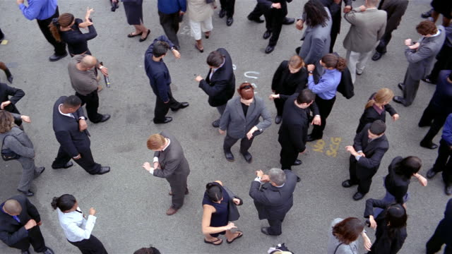 High angle wide shot overhead shot of crowd of businesspeople walking back and forth / stopping + checking watch