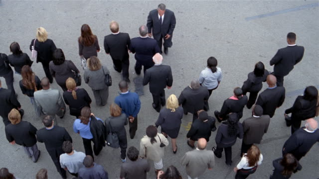 high angle wide shot overhead view of crowd of businesspeople walking / man walking towards crowd - distinguersi dalla massa video stock e b–roll