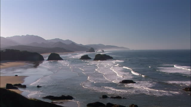 High angle wide shot Pacific Ocean and coastline/ zoom in rocks/ Cannon Beach, Oregon