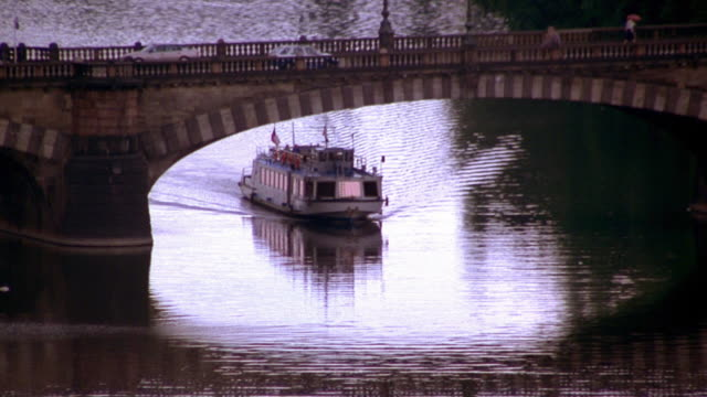 high angle wide shot pan boat passing under bridge on vltava river / prague, czech republic - vltava river stock videos & royalty-free footage
