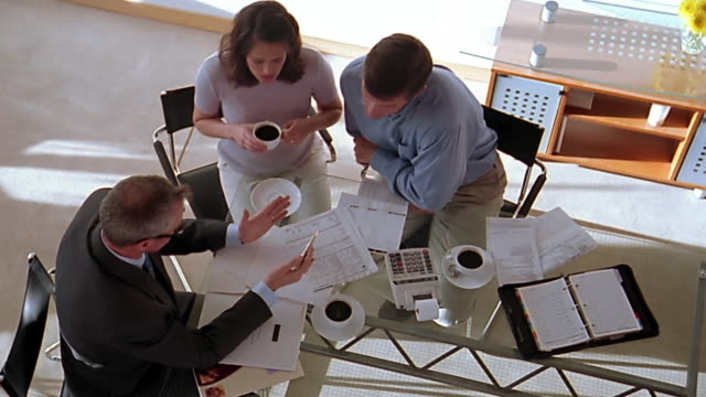 high angle wide shot pan couple meeting with financial advisor - financial advisor stock videos & royalty-free footage