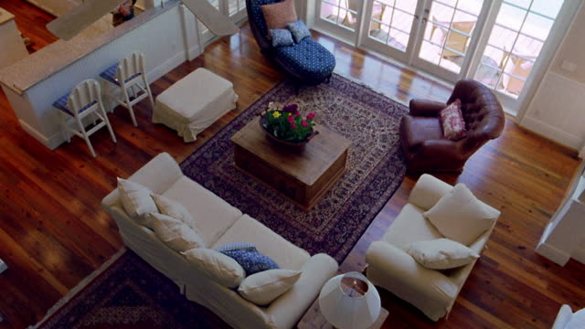 high angle wide shot pan empty living room in house - rug stock videos & royalty-free footage