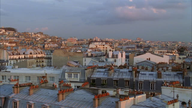 high angle wide shot pan over rooftops in montmartre at twilight / view of sacre coeur / paris, france - basilique du sacre coeur montmartre stock videos & royalty-free footage