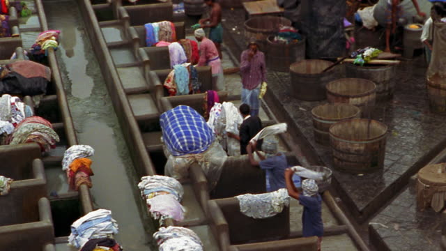 high angle wide shot pan people hand washing clothing in laundry pit / bombay - mumbai stock videos & royalty-free footage