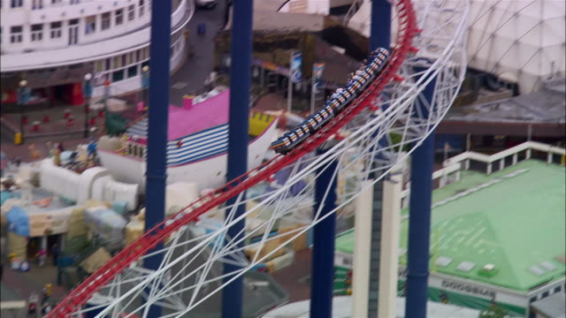 high angle wide shot pan rollercoaster/ blackpool, england - blackpool stock-videos und b-roll-filmmaterial