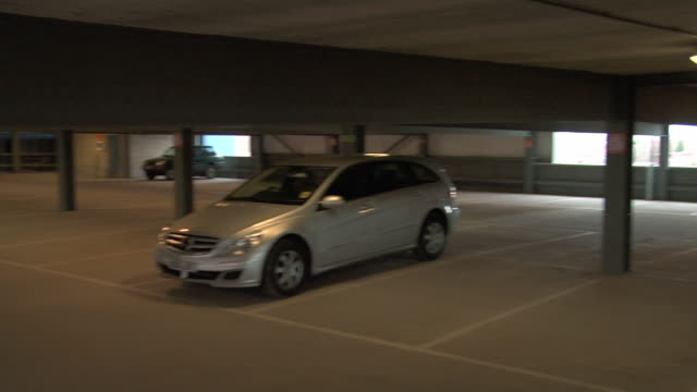 high angle wide shot pan security camera-like view of nearly empty parking garage/ england - 駐車場点の映像素材/bロール
