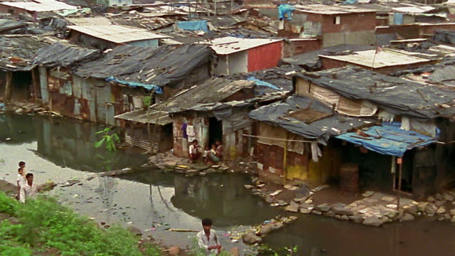 vidéos et rushes de high angle wide shot pan shacks on banks of river or stream / bombay - cahute