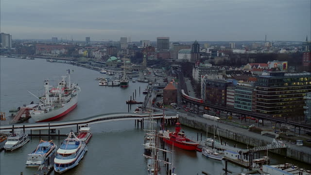 high angle wide shot pan ships docked in harbor over city of hamburg with train traveling in foreground / germany - tornspira bildbanksvideor och videomaterial från bakom kulisserna