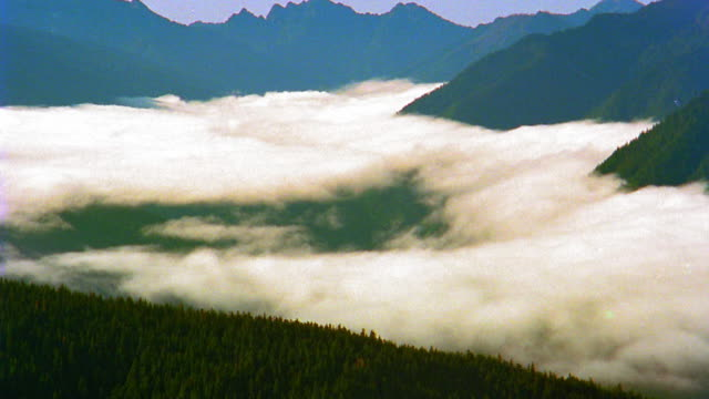 high angle wide shot pan time lapse clouds or fog in mountain valley / olympic mountains, olympic peninsula, washington - mountain range stock videos & royalty-free footage
