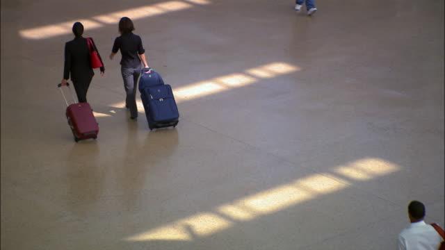 high angle wide shot pan two businesswomen walking through airport pulling luggage/ seattle - 引く点の映像素材/bロール