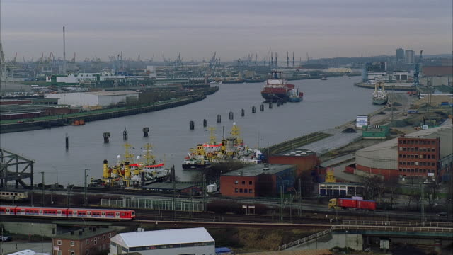 vídeos y material grabado en eventos de stock de high angle wide shot pan view of factories and canals with trains traveling in foreground on cloudy day/ hamburg, germany - tren elevado