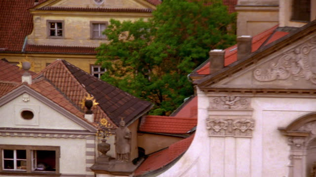 high angle wide shot pan zoom out buildings and rooftops of prague old town / czech republic - st frantisek church stock videos and b-roll footage