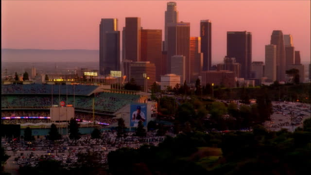 High angle wide shot panning from downtown skyline to Dodger Stadium / dusk / Los Angeles, California