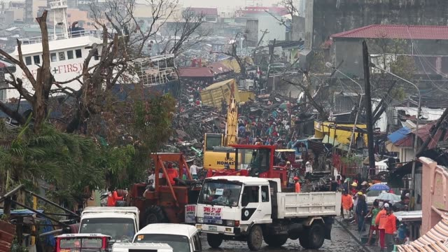 vídeos de stock, filmes e b-roll de high angle wide shot, people make their way through a street devastated by the typhoon. typhoon haiyan, which ripped through philippines on november... - high street