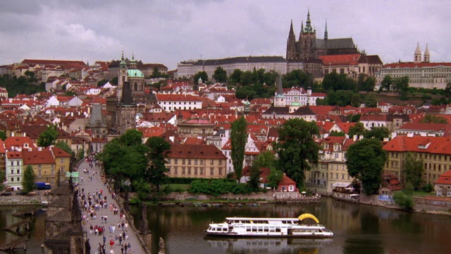 high angle wide shot people on bridge over vltava river with city in background / prague, czech republic - フラッチャニ城点の映像素材/bロール