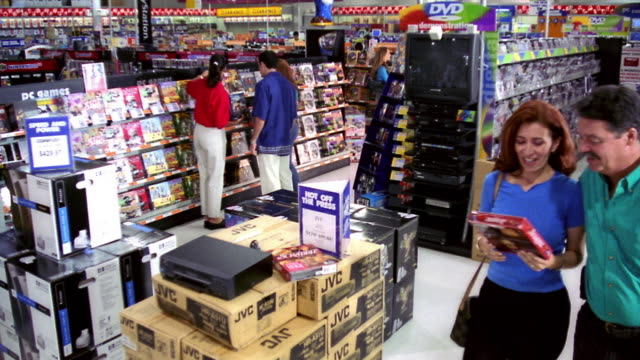 high angle wide shot PAN people shopping in electronics + computer store / couple carrying software box
