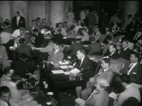 vídeos de stock, filmes e b-roll de b/w 1953 high angle wide shot people sitting at desks standing in crowded room / armymccarthy hearings - senado governo