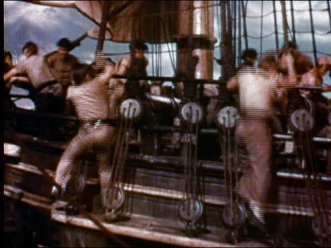 1956 high angle wide shot pirates fighting on deck of ship / man swinging on mastline / audio - seeräuber stock-videos und b-roll-filmmaterial