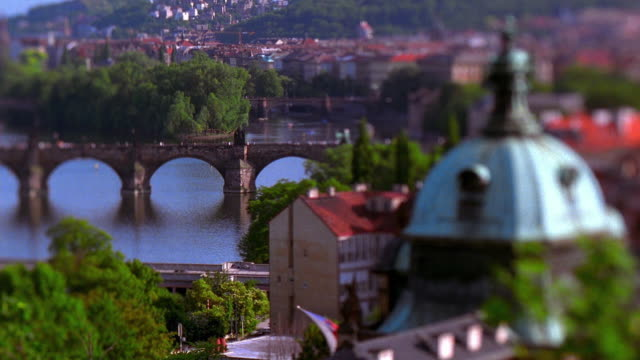 vídeos de stock e filmes b-roll de high angle wide shot rack focus charles bridge on vltava river with domed building in foreground / prague, czech republic - ponte carlos