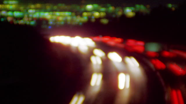 high angle wide shot rack focus time lapse traffic on highway with city lights in background / los angeles, california - traffic点の映像素材/bロール