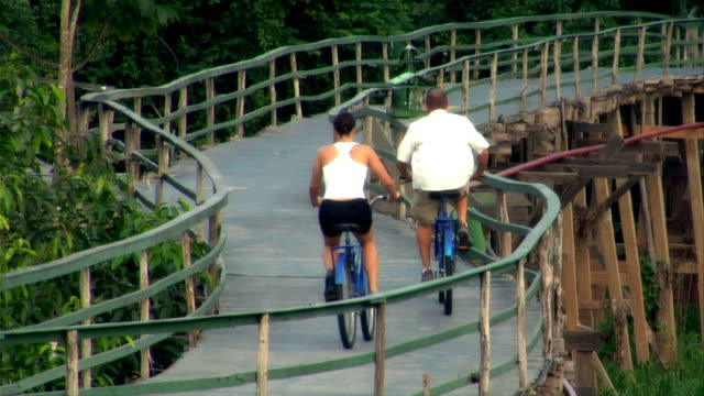 high angle wide shot rear view of man and woman riding bicycles on wooden bridge toward rainforest / the amazon, brazil - paar mittleren alters stock-videos und b-roll-filmmaterial