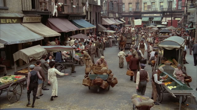 high angle wide shot recreation of early 20th century new york city street market - korb stock-videos und b-roll-filmmaterial