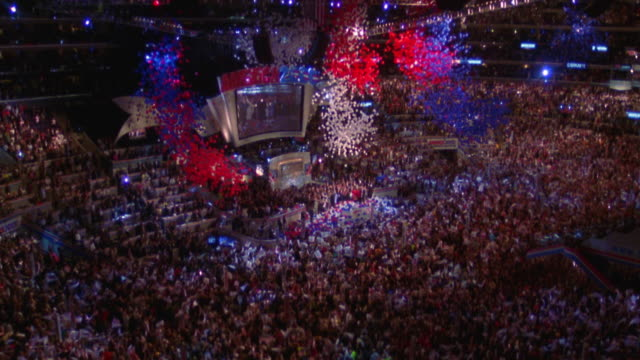 high angle wide shot red, white + blue balloons falling on crowd at Democratic National Convention / Los Angeles